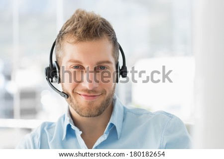 Handsome call centre agent wearing a headset in creative office - stock photo