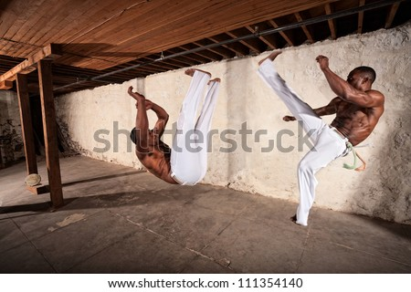 Handsome capoeria martial artists perform flying kicks - stock photo
