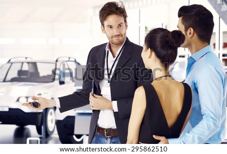 Handsome car dealer showing around young couple in showroom. - stock photo