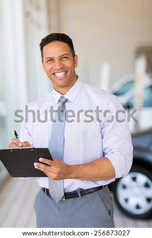 handsome car dealership salesman working in showroom