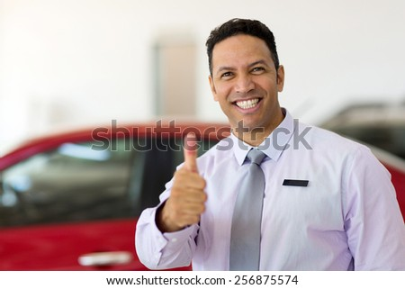 handsome car salesman thumb up at car dealership - stock photo