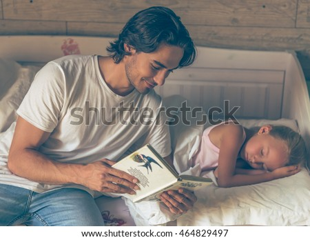 Handsome caring father is reading a book to his cute little daughter before bed and smiling, girl is already sleeping in her bed at home