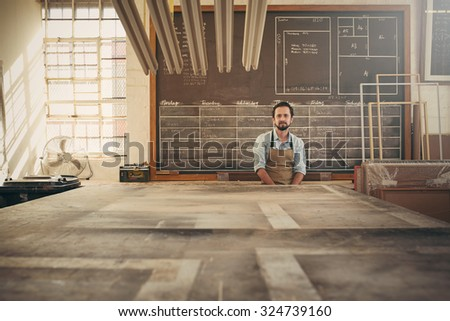 Handsome carpeter businessman sitting in his workshop in front of a daily schedule drawn on a chalk board, looking confidently at the camera - stock photo