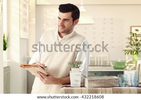 Handsome casual caucasian charming man at vintage italian home with newspaper in hand. Wearing sleeveless sweater, standing at dining room, wondering, thinking, smiling, bristly. - stock photo