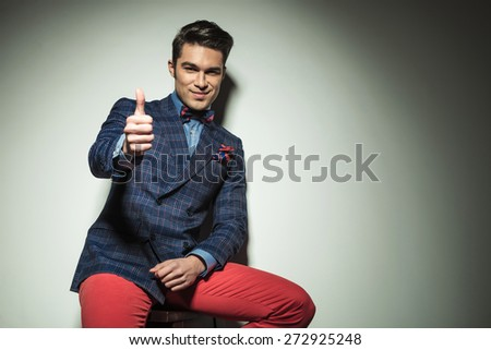 Handsome casual fashion man sitting on a chair while showing the thumbs up gesture. - stock photo