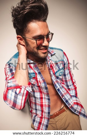 Handsome casual man looking away from the camera while holding his hand a this neck, with one hand in his pocket. - stock photo