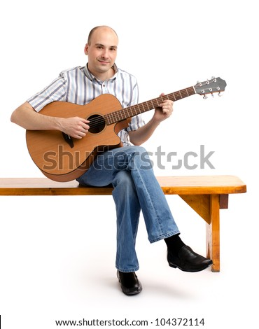 Handsome casual man with guitar sitting on bench. Isolated on white background. - stock photo