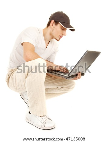 Handsome casual sitting man with open laptop and is looking on a screen on white background