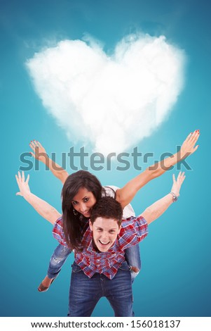 Handsome casual young man carrying his girlfriend on his back, playing in front of a heart shaped cloud