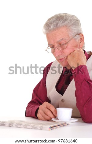 Handsome caucasian aged male sits at a table with a newspaper on a light background
