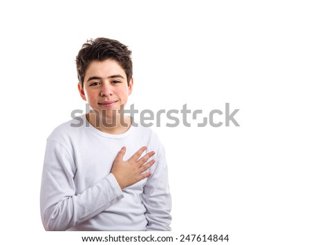 Handsome Caucasian boy with acne-prone skin in a white long sleeved t-shirt smiles keeping his right hand on the heart - stock photo