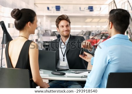 Handsome caucasian businessman handing over car keys at dealership to a young couple. Sitting at table, eye contact, smiling.