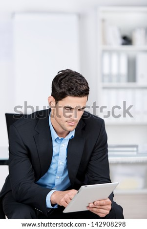 Handsome caucasian businessman sitting in a chair by the office, and working with a tablet - stock photo