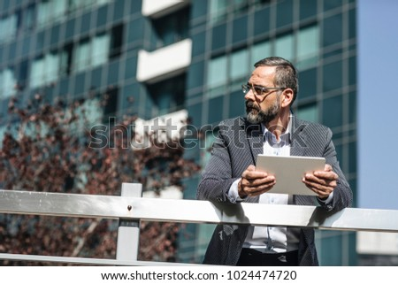 Handsome Caucasian businessman standing by the glass building and holding tablet.