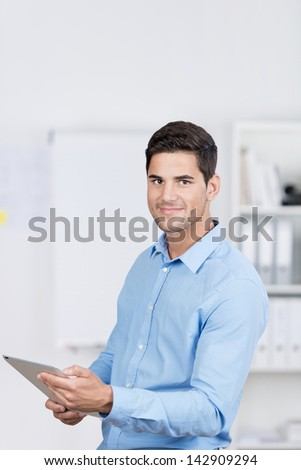 Handsome caucasian businessman standing in the office, and working with a tablet