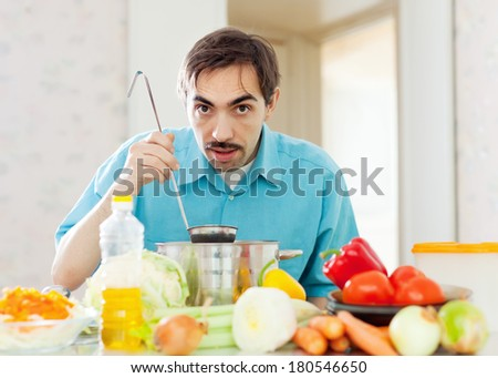 handsome caucasian guy eats from pan at home - stock photo