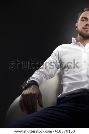 Handsome caucasian guy in white shirt sitting in chair, looking front over black background. Toned