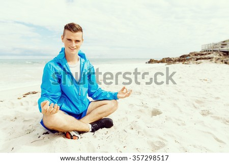 Handsome caucasian male doing exercises on beach