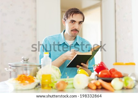 handsome caucasian man cooking  vegetables with cookbook at kitchen - stock photo