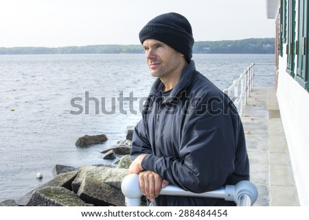 Handsome Caucasian man dressed in jacket and black cap leans against railing of lighthouse at end of breakwater in Rockland, Maine as he gazes peacefully into the distant ocean - stock photo