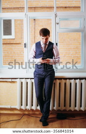 Handsome Caucasian Man In Business Attire Staying In Room Near Window And Holding Mobile Phone - stock photo