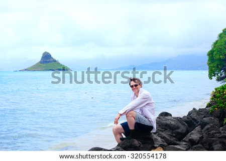 Handsome Caucasian man in forties sitting on rocky shore of hawaiian beach, by Chinaman's Hat island - stock photo