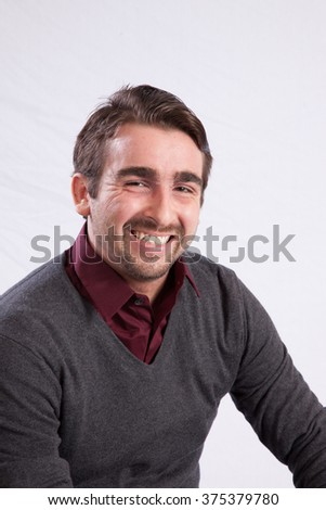 Handsome Caucasian man in suit coat and glasses, looking at the camera with a smile - stock photo