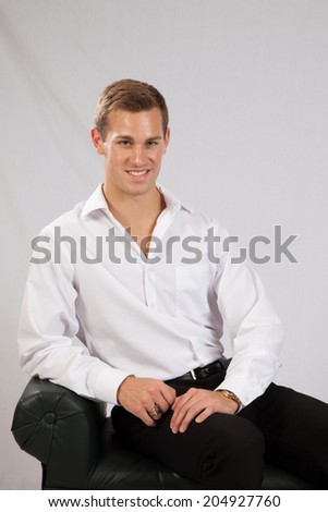 Handsome Caucasian man in white shirt and black slacks, sitting and looking   at the camera with a smile