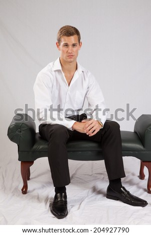Handsome Caucasian man in white shirt and black slacks, sitting and looking thoughtfully at the camera