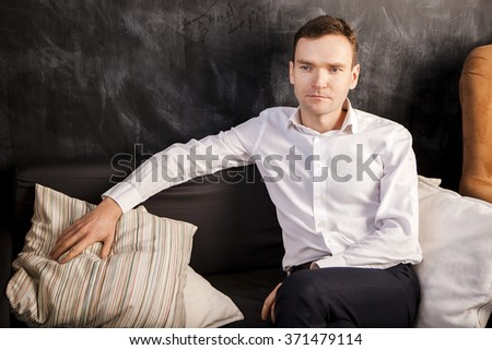handsome caucasian man sitting on a couch in a white shirt horizontal view relaxed looking thoughtfully sideways - stock photo
