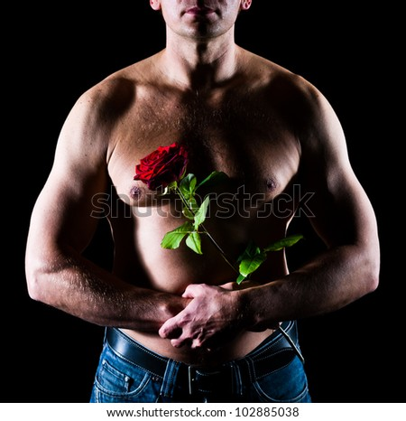 Handsome caucasian man to keep a rose front of chest - stock photo