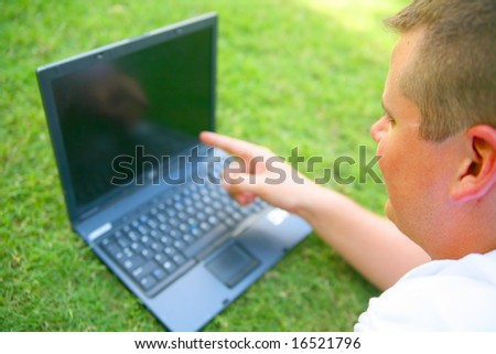 handsome caucasian man using computer outdoor in grassy park