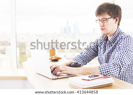 Handsome caucasian man using notebook on wooden desktop with coffee, croissant, smartphone and notepads on blurry city background - stock photo