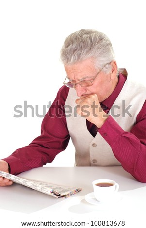 Handsome caucasian nice aged male sits at a table with a newspaper on a light background