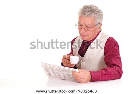 Handsome caucasian old male sits at a table with a newspaper on a light background