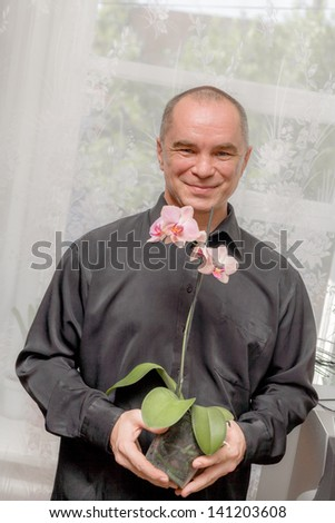 Handsome caucasian 40s man smiling portrait on grey background with black shirt holding orchid in pot. A business man having a blooming pink orchid - stock photo