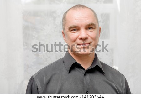 Handsome caucasian 40s man smiling portrait on grey background with black shirt. Portrait of handsome smiling man. One mature caucasian man front view, handsome man smiling portrait indoors - stock photo