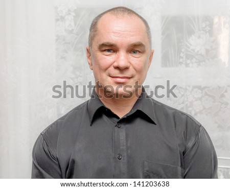Handsome caucasian 30s man smiling portrait on indoor background with black shirt. Portrait of handsome smiling man. One mature caucasian man front view, handsome man smiling portrait indoors - stock photo