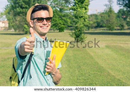 Handsome caucasian student with the thumb up - concept about people, education and lifestyle - stock photo
