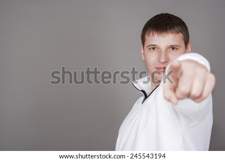 Handsome Caucasian Young Man Pointing Forward Using His Point Finger. Over Gray Background. Horizontal Image Composition - stock photo