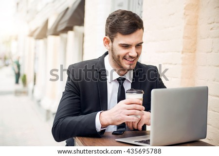 Handsome cheerful man using laptop - stock photo