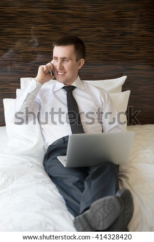 Handsome cheerful young business man sitting with laptop and talking on phone. Businessman working at home or in trip. Businessperson sitting on bed in formal wear and his shoes on - stock photo