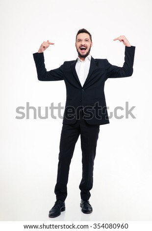 Handsome cheerful young businessman in black suit laughing and pointing on himself with both hands over white background - stock photo
