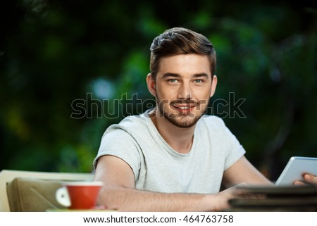 Handsome cheerful young man sitting at the table in open-air cafe holding tablet looking in camera.