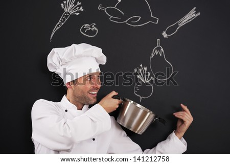 Handsome chef catching ingredients for soup - stock photo