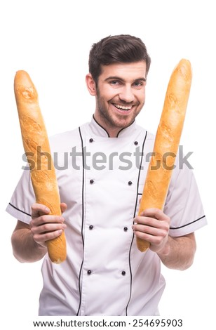 Handsome chef is holding a baguettes, isolated on white background.