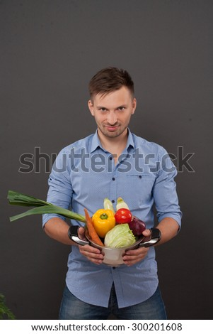 Handsome chef keeping pan with fresh vegetables ondarkgrey. Man in blue shirt smiling in the kitchen, he is going to prepare gaspacho. - stock photo