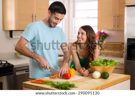 Handsome chef man and beautiful woman on a date chopping vegetables and a nutritious meal and salad - stock photo