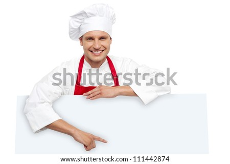 Handsome chef pointing at white billboard. Standing behind it and smiling