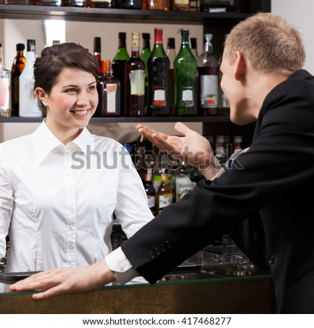 Handsome client talking with cute girl bar